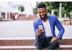 一名身穿蓝色夹克的非洲裔美国男子使用电话_4757208