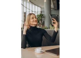 一名年轻的女商人在咖啡馆里用笔记本电脑工_13377039