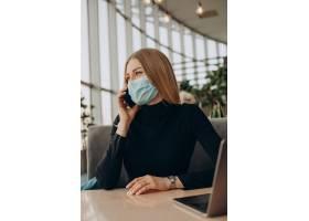 一名戴面具的年轻女商人在咖啡馆里用笔记本_13377050