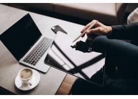 一名正在平板电脑上工作的男子在桌子旁近距_8828010