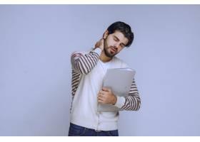 一名男子完成了项目拿着文件夹疲惫的样_13406770
