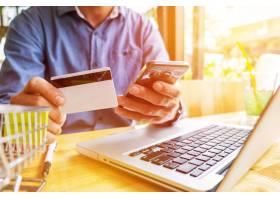 一名男子手里拿着信用卡用笔记本电脑键盘_1202168