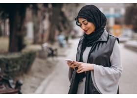 一名穆斯林妇女在外面的街道上使用电话_4410708