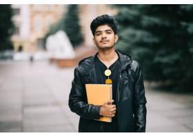 一名英俊的印度年轻学生站在街上手里拿着_9077337
