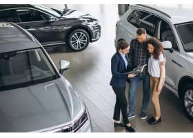 一对年轻夫妇在汽车展厅与销售人员交谈_5157713