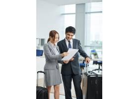 一男一女穿着西装拿着手提箱站在办公室_5576480