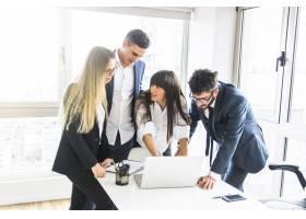 一群商务人士站在办公室看办公室里的笔记本_3165823