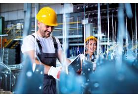 身穿制服头戴黄色防护安全帽的工人在工厂_11035665