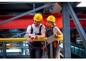 身穿防护装备的工厂工人站在生产大厅分享想_11035691