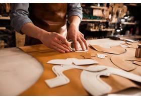 鞋匠测量和裁剪皮革的特写_7573216