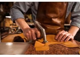 鞋匠用皮革工作的特写镜头_7573231