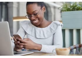 高兴的女文案在智能手机上阅读正面信息坐_9591287