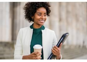 黑人女商人的肖像手里拿着一杯咖啡和一个_12740343