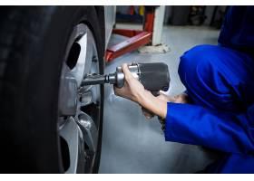用气动扳手固定汽车车轮的女机械师的手_1005115