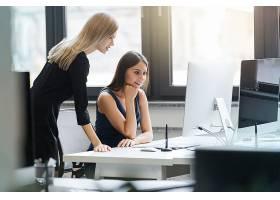 漂亮的女人们在办公室里一起在电脑前工作_7337452