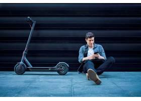 潮人坐在地上坐在他的电动滑板车旁边背_11036641