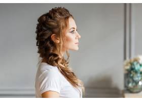 灰墙背景下年轻漂亮女孩的侧影_3337217