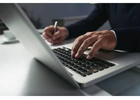 男性手在笔记本电脑键盘上打字的侧视图_5698945