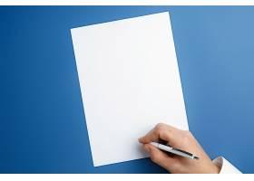 男性手持钢笔在蓝色墙上的空白纸上书写文_12786657
