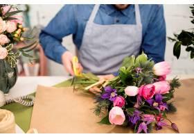 男性花店店主剪纸包装花束的特写_4056838