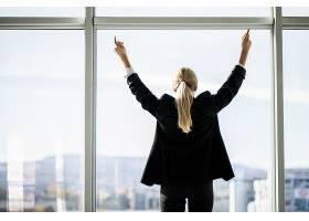 自信的女商人站在办公室窗前张开双手享受_8471801