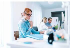 自信的年轻女商人在办公室用笔记本电脑工作_3492561