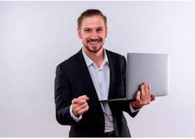 英俊的商务人士穿着西装拿着笔记本电脑_12525504