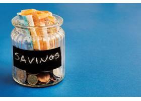 蓝色背景上印有欧元纸币和硬币的储蓄瓶_3063809