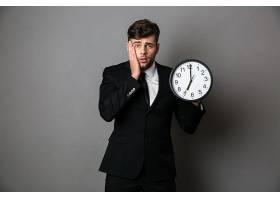 西装革履的工人拿着钟的特写照片_7439213
