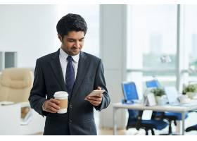 西装革履的男子站在办公室里端着外卖咖啡_5576505