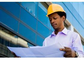 戴着头盔的专业建筑师的肖像看着现代建筑_9882710