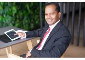 快乐的印度商人在咖啡馆使用平板电脑_1121942