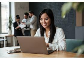 快乐的年轻亚洲女商人使用笔记本电脑_6514539