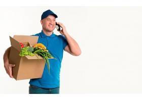 快乐的送货员一边打电话一边拿着杂货箱_6292817