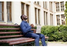 快乐的非裔美国人坐在外面的长凳上用笔记本_2437956