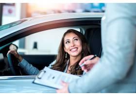 快乐的顾客在当地的汽车经销商购买全新的汽_11136262