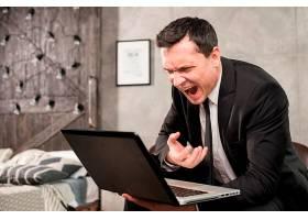 愤怒的商人在家里对着笔记本电脑大喊大叫_4360411