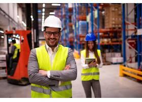 成功的仓库工人或主管交叉双臂站在大型仓储_11451275