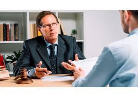 成熟的律师在法庭上与委托人讨论合同_3105561