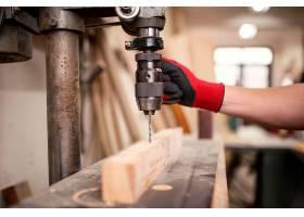 木工车间和钻孔机在一块木质材料上工作_11451165