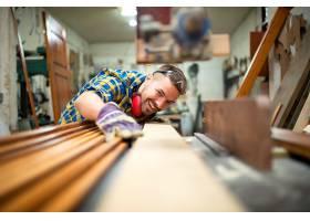 木工车间里有经验的木工在机器上切割木板的_11137134