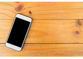 木桌背景黑屏手机带有复制空间的俯视图_1253564