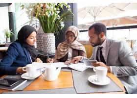 多元文化商业伙伴在咖啡馆讨论合同_5890441