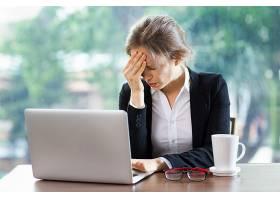 头疼得厉害的女人拿着笔记本电脑喝着咖啡_982813