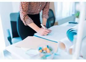 女商人在办公室里用不干胶纸条写字的特写_3492503