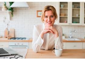 女商人端着咖啡杯和笔记本电脑坐着_4299081