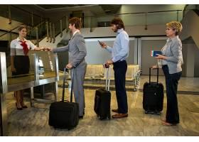 女工作人员在值机柜台检查旅客登机牌_8236040