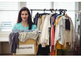 女志愿者在捐赠箱里拿着衣服_1005868