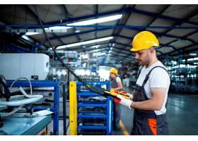 工厂工人穿着制服戴着安全帽在生产大厅_11035576