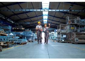 工厂工人走过大的生产大厅_11034323